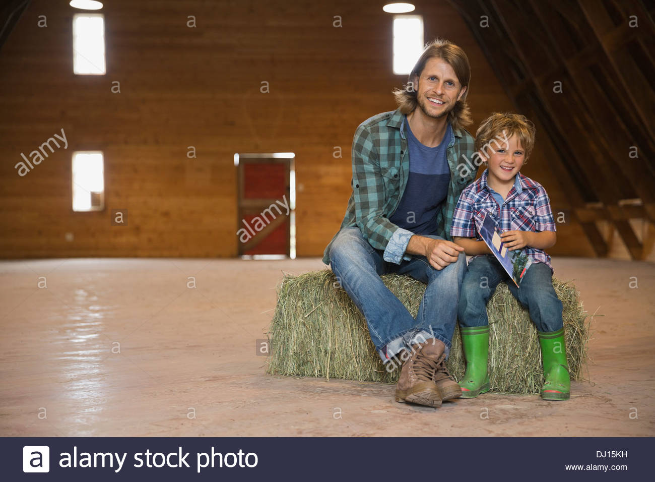 Full length portrait of father and son sitting on hay bale in barn - Stock Image