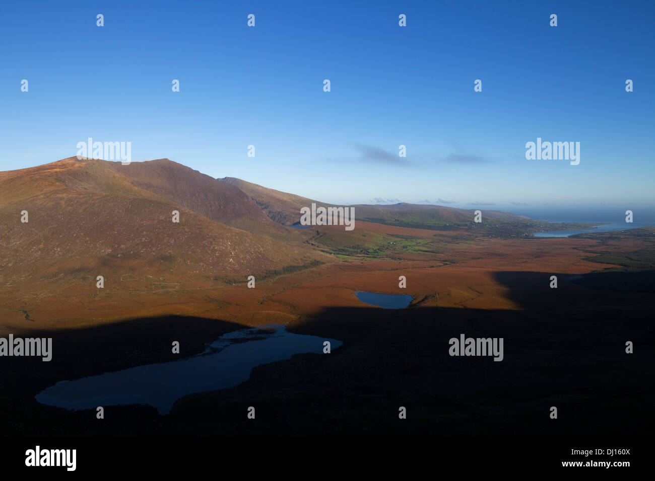 Lakes below the Conor Pass with Brandon Mountain and distant Castlegregory, Dingle Peninsula, County Kerry, Ireland - Stock Image