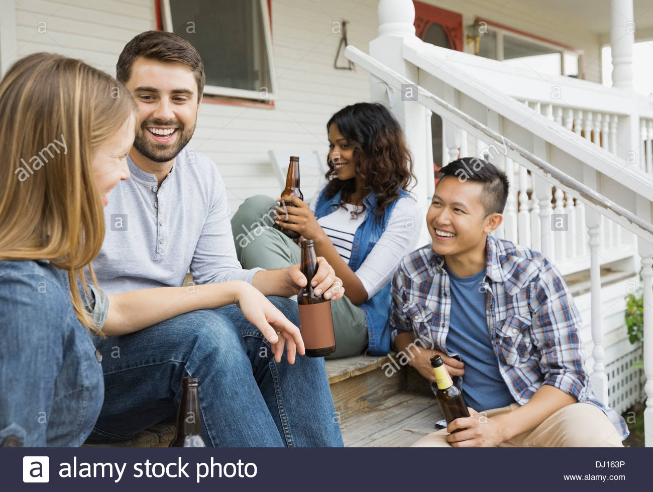 Group of friends enjoying drinks on porch - Stock Image
