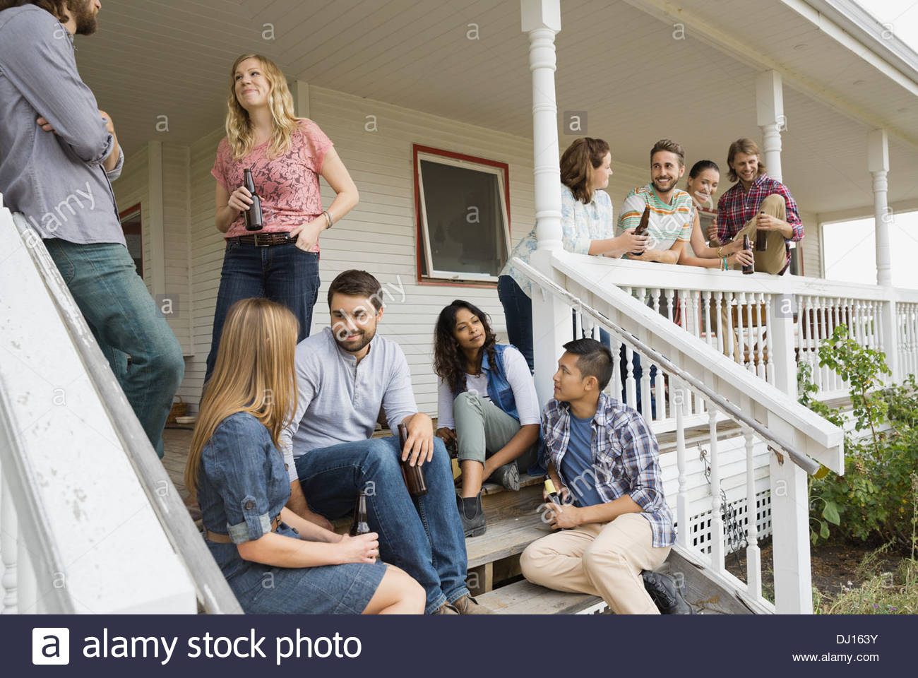 Multiethnic friends enjoying party on porch - Stock Image