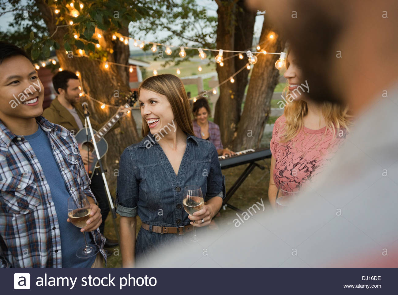Multiethnic friends enjoying outdoor party with band playing - Stock Image