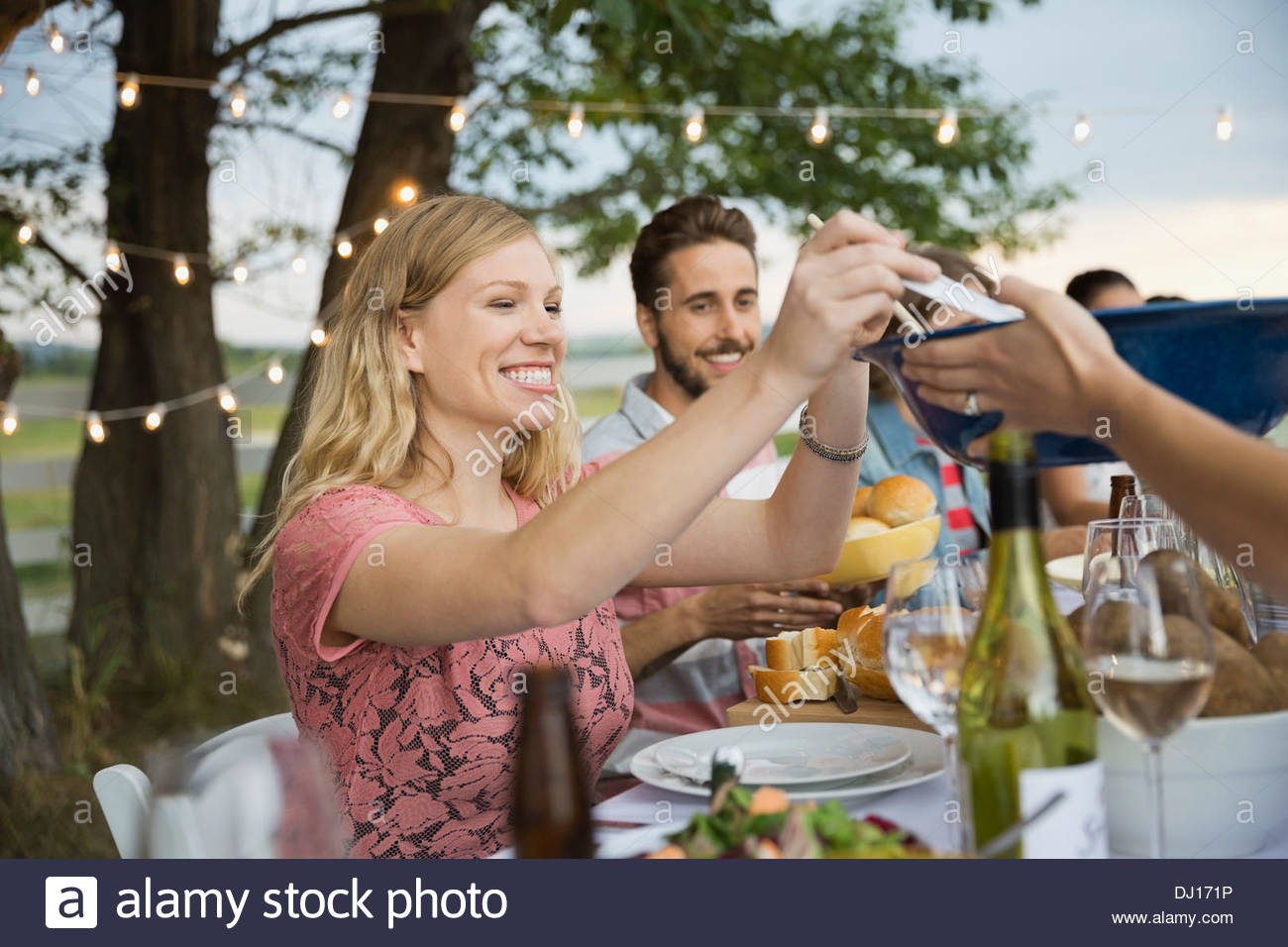 Friends sitting together at an outdoor dinner party - Stock Image