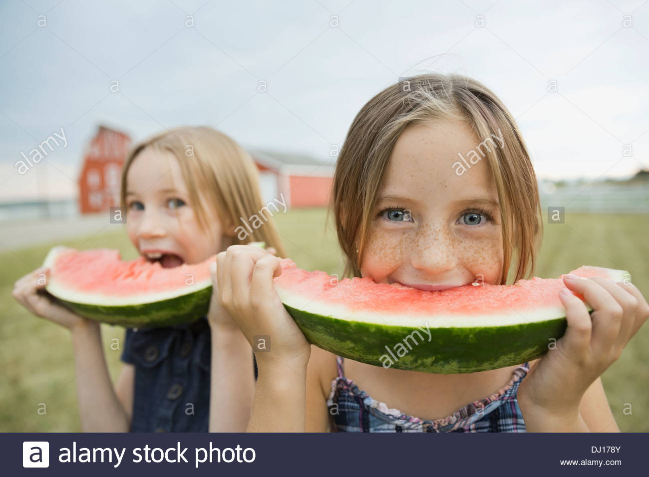 Portrait of girls eating watermelon slices outdoors - Stock Image
