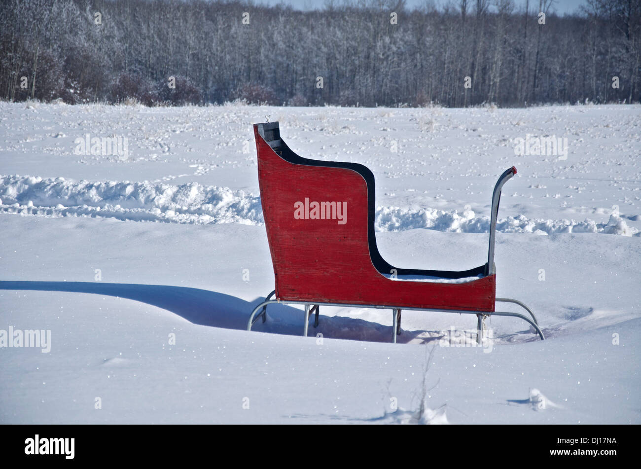 A rustic wooden red sleigh brightens up a field of freshly fallen snow on a sunny winter day. - Stock Image