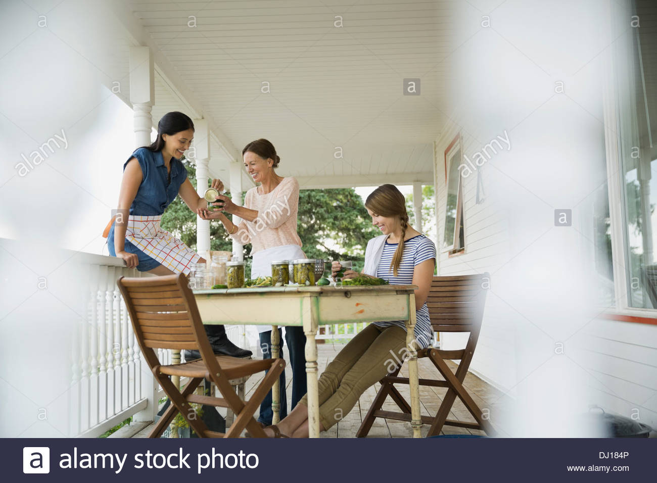 Mother and daughters canning vegetables on porch - Stock Image