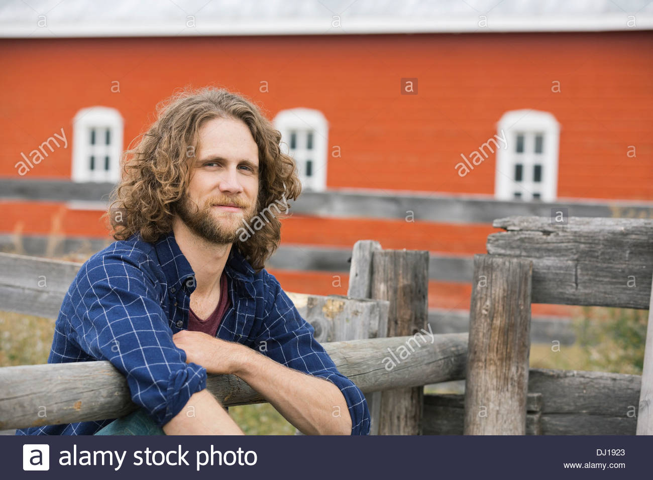 Portrait of happy man leaning against fence - Stock Image