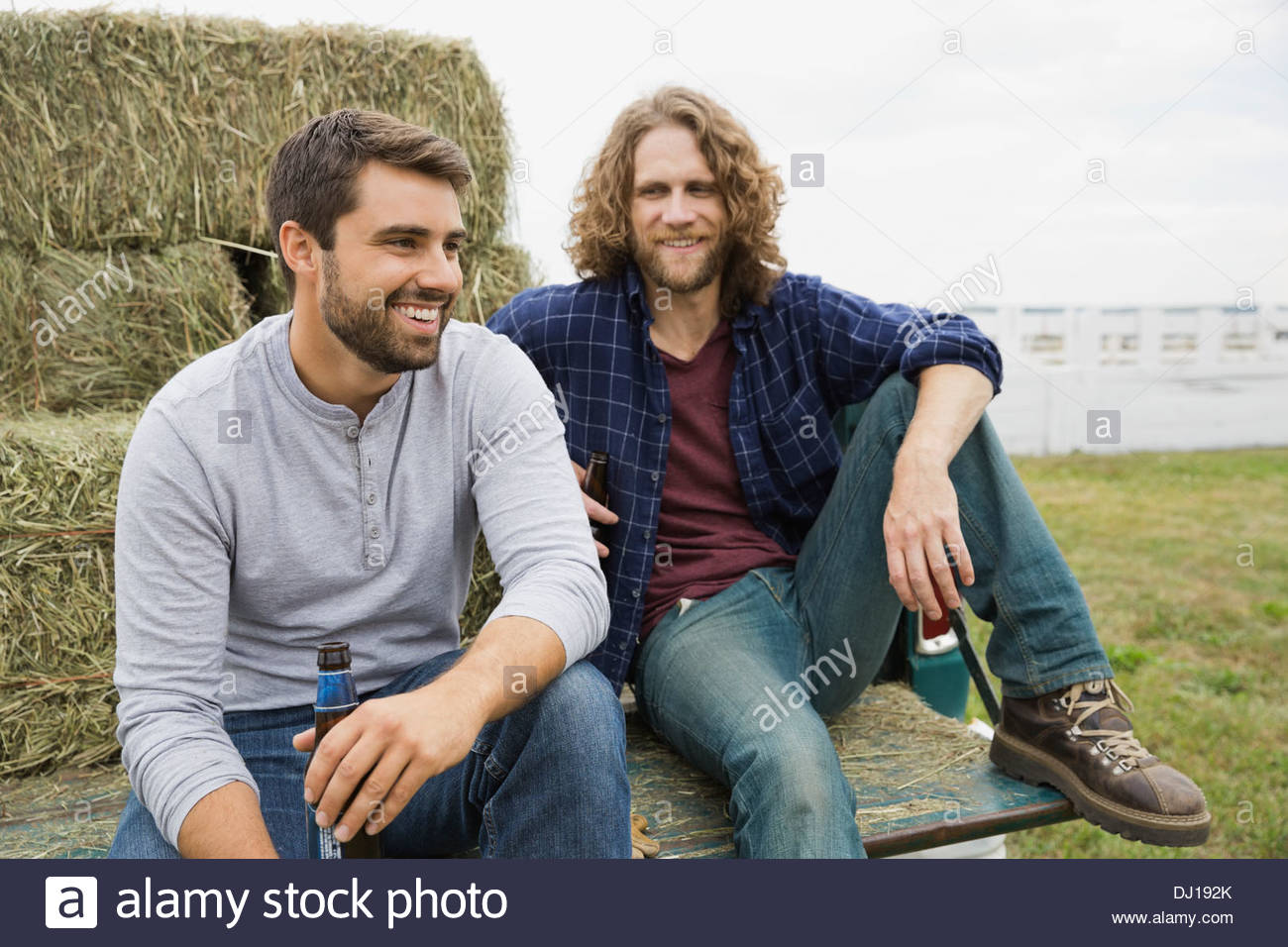 Male friends sitting in back of pick-up truck - Stock Image