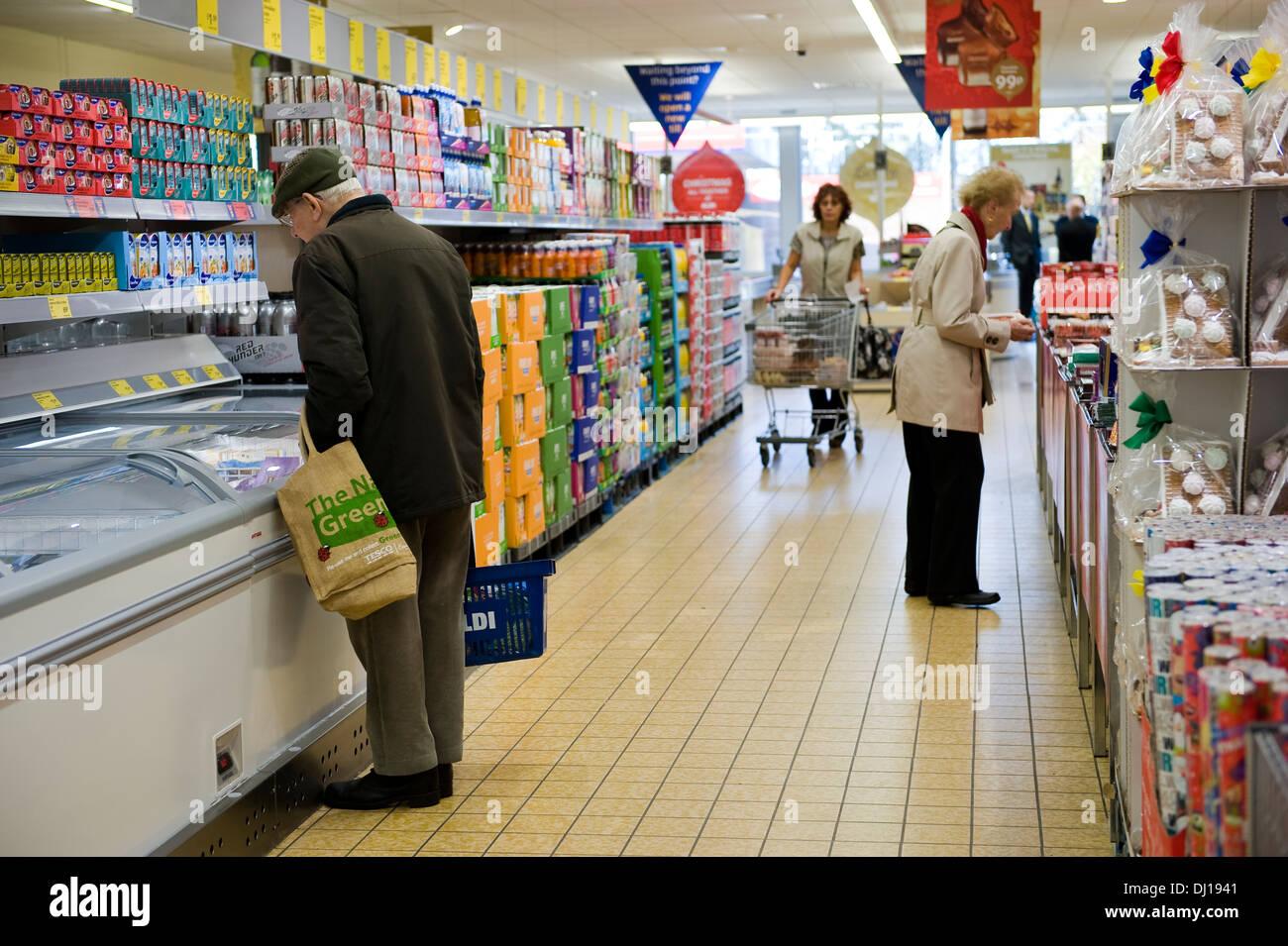 A pensioner shopping for frozen food in UK budget Supermarket Aldi. - Stock Image