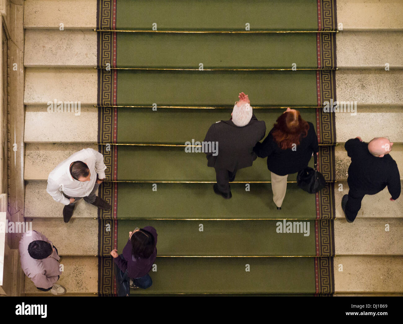 Opera Patrons chat and climb the marble stair. Opera goers discuss the opera at the intermission and climb back to their seats. - Stock Image