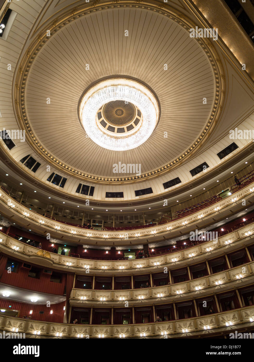 Ceiling and balconies of the main hall at Vienna State Opera. A large chandelier dominates the circular space. - Stock Image