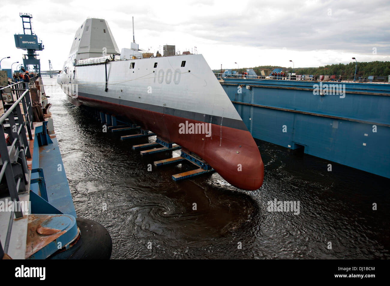 The Zumwalt-class guided-missile destroyer USS Zumwalt is floated out of dry dock at the General Dynamics Bath Iron Works shipyard October 28, 2013 in Bath, Maine. The ship, the first of three Zumwalt-class destroyers is the latest generation of naval technology. - Stock Image