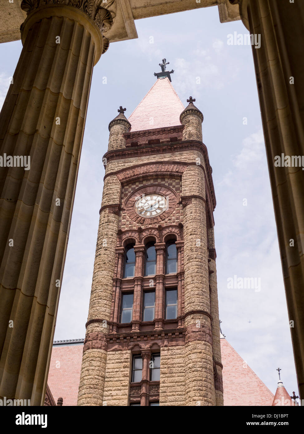 Cincinnati City Hall Clock tower. Framed by the tall Grecian columns of the Cathedral of St. Peter in Chains. Stock Photo