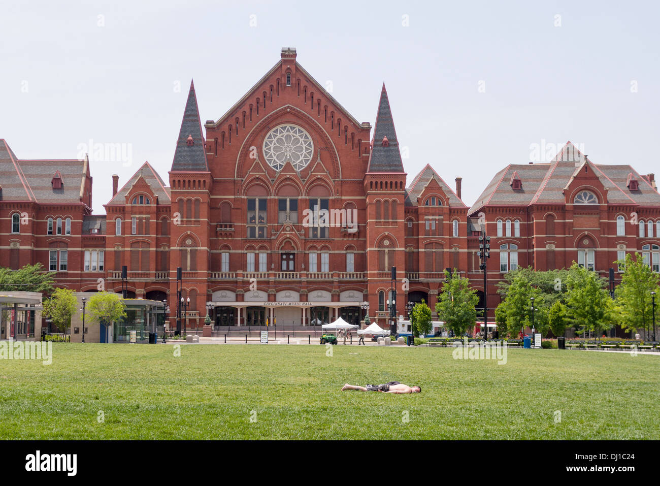 Cincinnati Music Hall with Sunbather. A young man catches a few spring rays on the lawn in front of the red brick Stock Photo