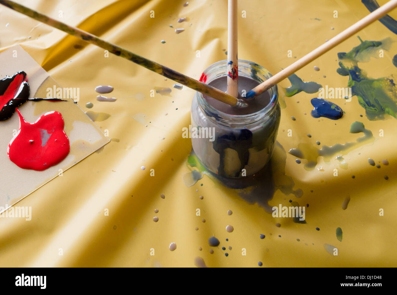 After Painting. Three brushes in a dirty pot of water on a yellow table cloth with spots of paint scattered. - Stock Image