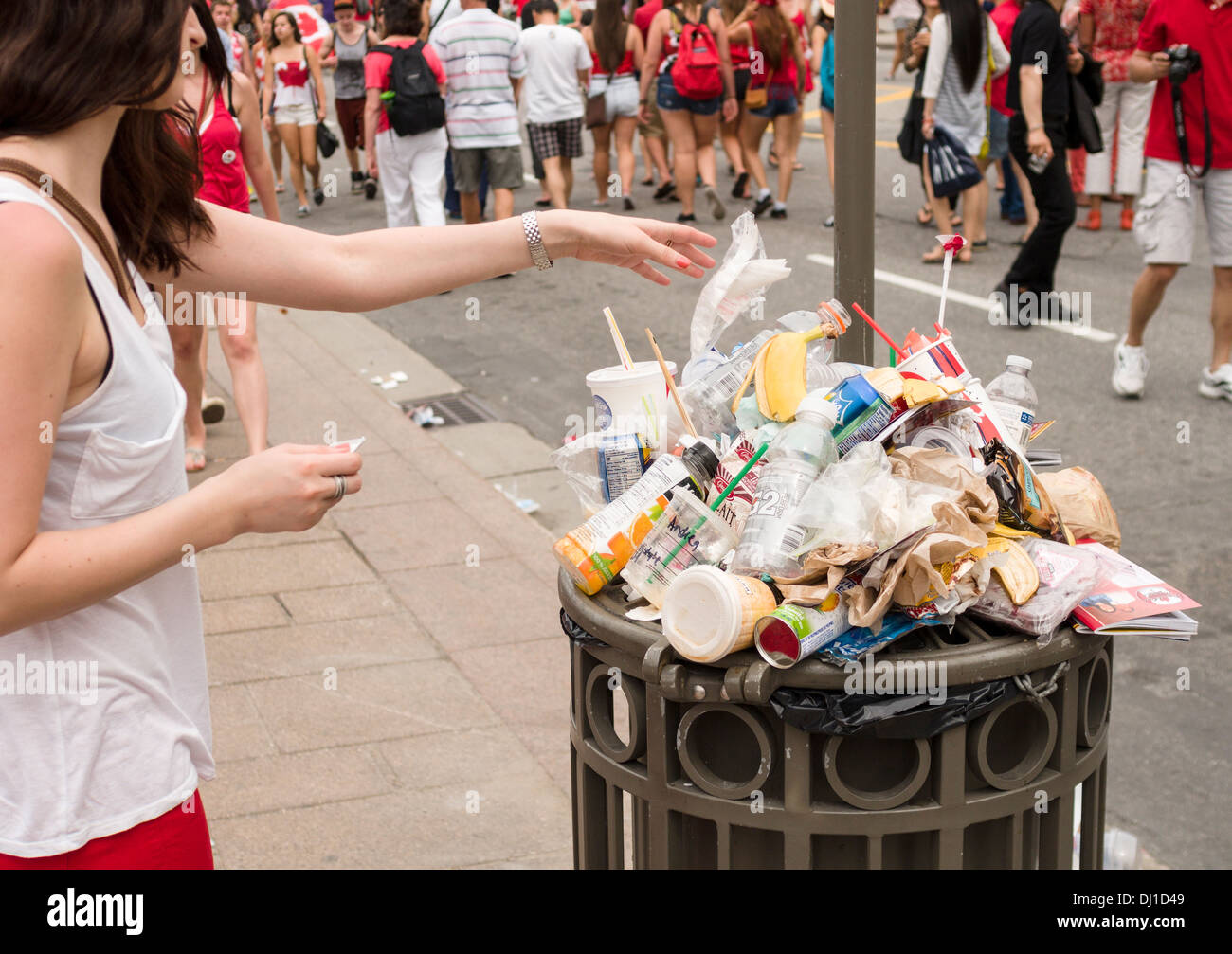 Full -- Overflowing Trash. A street side trash bin overflows with waste on a busy Canada holiday afternoon. - Stock Image