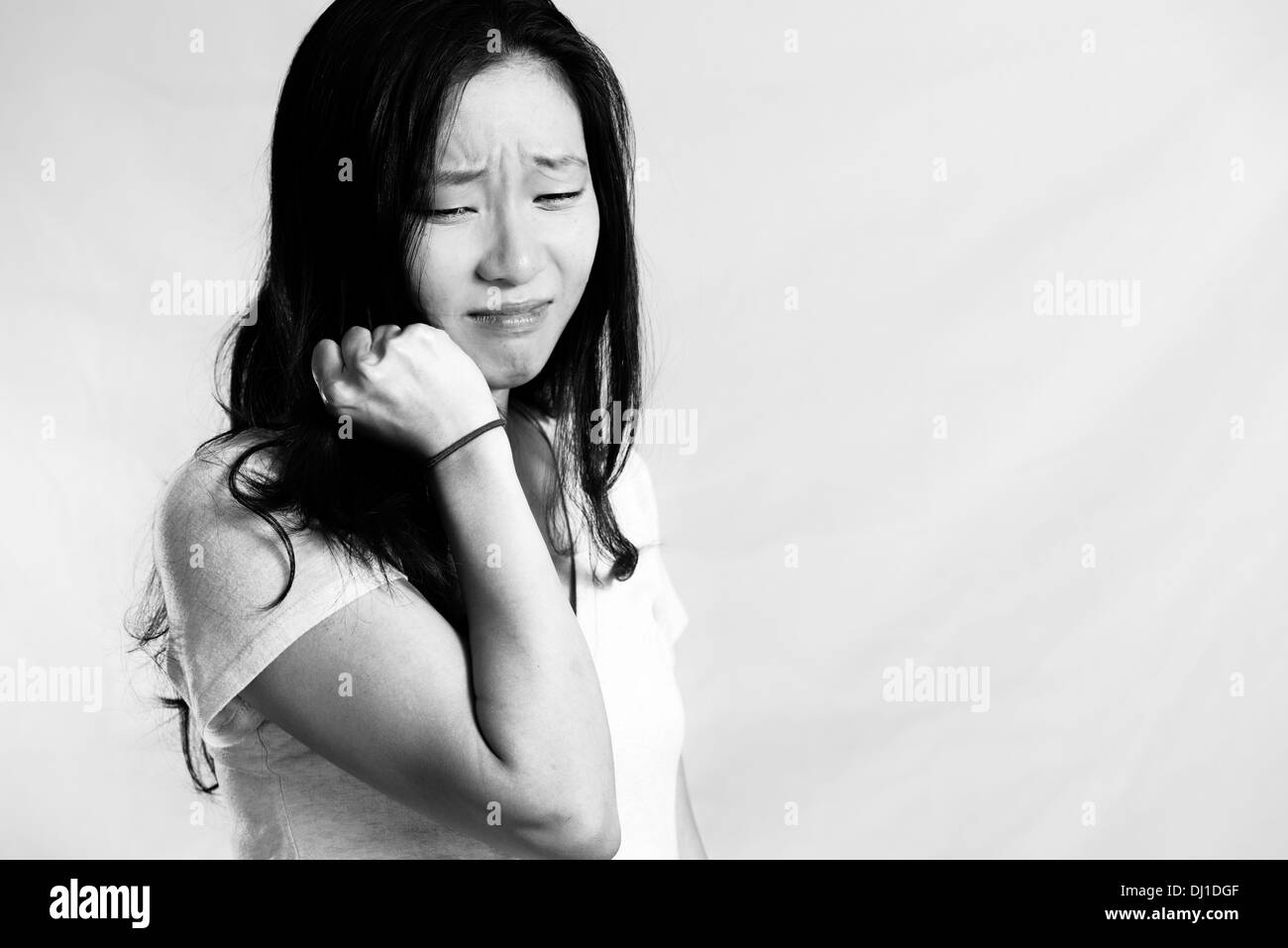 Portrait of young woman crying while pulling her hair, black and white style - Stock Image