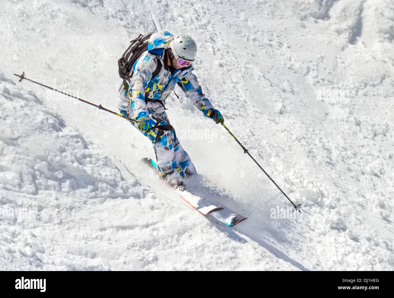 Man skier on a steep slope in the mountains - Stock Image