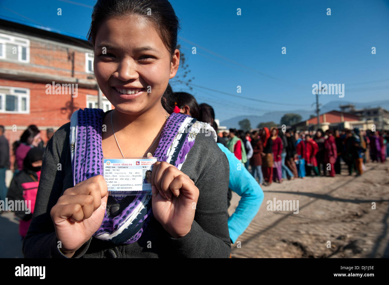 Kathmandu, Nepal. 19th Nov, 2013. Tika Shreshta, an eighteen years old girl, holds her voters card while in queue to cast her vote for the first time.Over 12 million eligible voters flocked to polling stations in a bid to elect Constituent Assembly. Last elections were held in 2008 when the Constituent Assembly failed to write a new constitution. Nepal has been struggling with political uncertainty since 2006 when street demonstrations forced then King Gyanendra to give up his authoritarian rule. Credit:  ZUMA Press, Inc./Alamy Live News - Stock Image