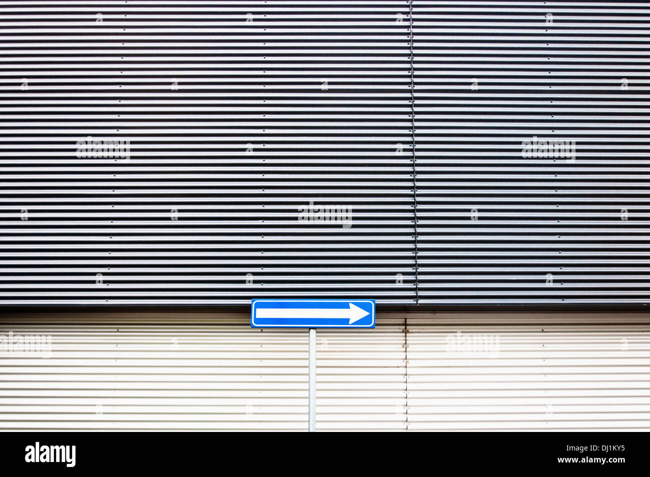 arrow road sign in front of wall of commercial building - Stock Image