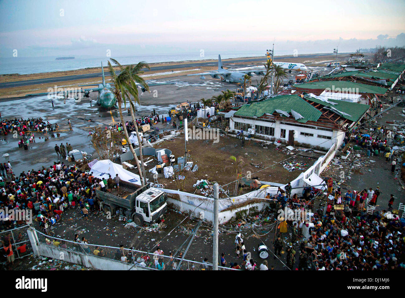 Residents gather at the the destroyed Tacloban Airfield for evacuation to Manila in the aftermath of Super Typhoon Haiyan November 14, 2013 in Tacloban, Philippines. - Stock Image