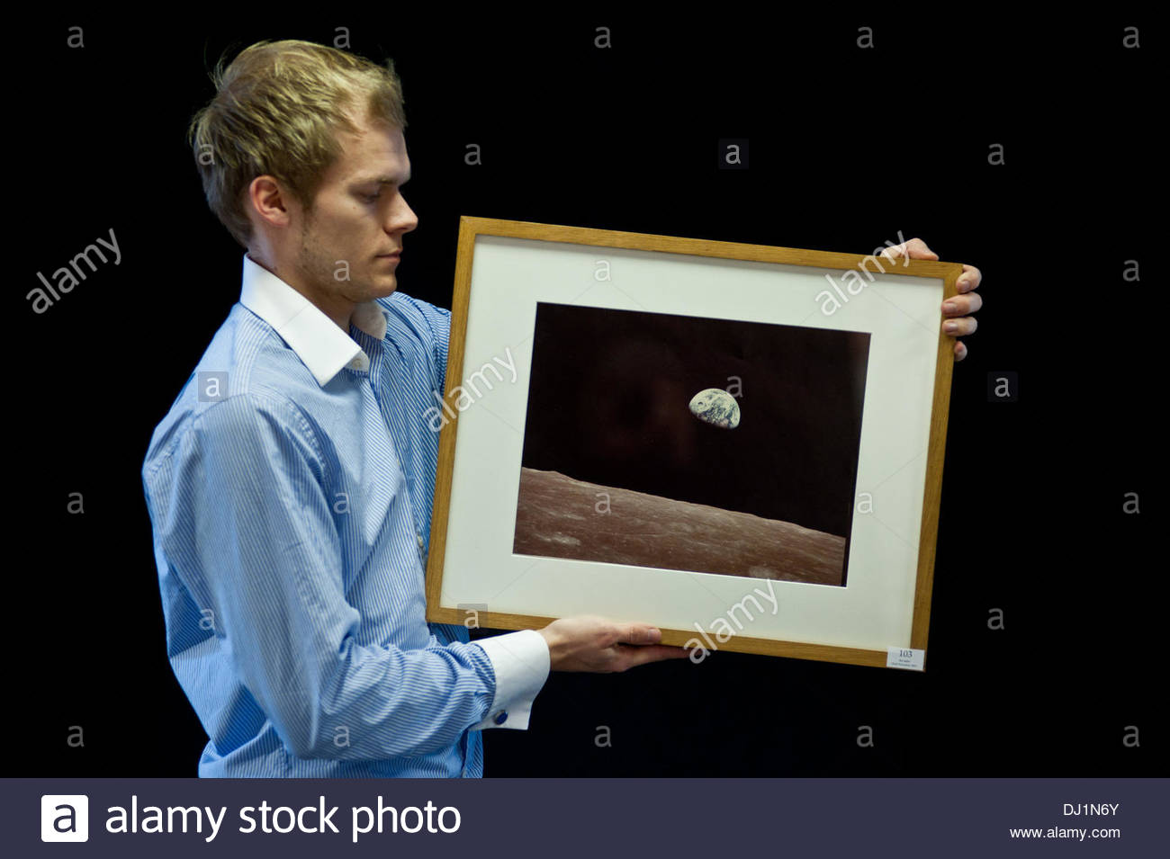 Alamy Exclusive: London, UK - 19 November 2013: Photography assistant Charles Hoey, looks at 'Earthrise, Apollo 8, 24 December 1968' by NASA/William Anders at the Dreweatts & Bloomsbury photography auction preview. The photograph estimated £600-800, will go to auction on the 22nd November. Credit:  Piero Cruciatti/Alamy Live News - Stock Image