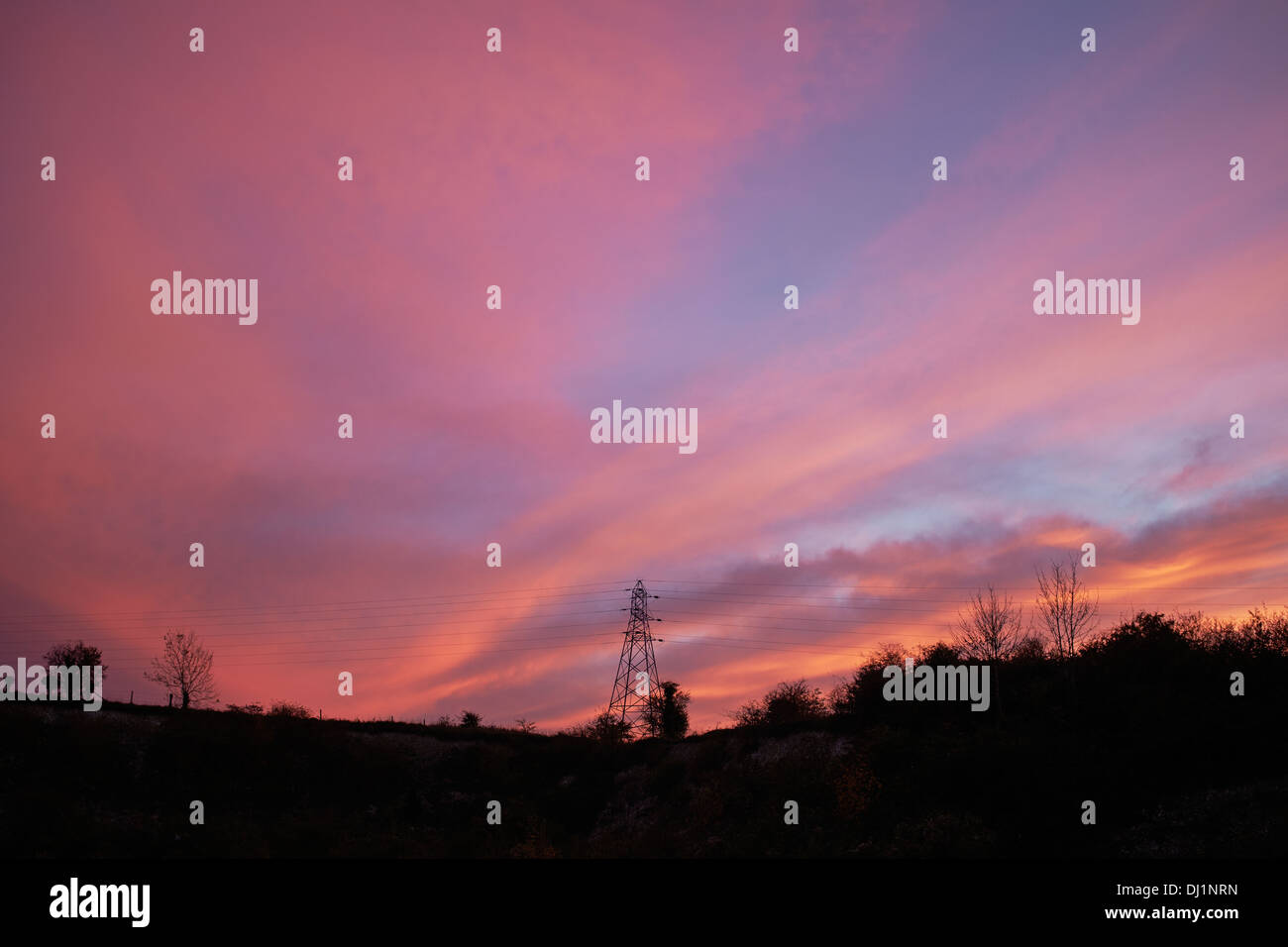 Red sunset behind an electricity pylon - Stock Image