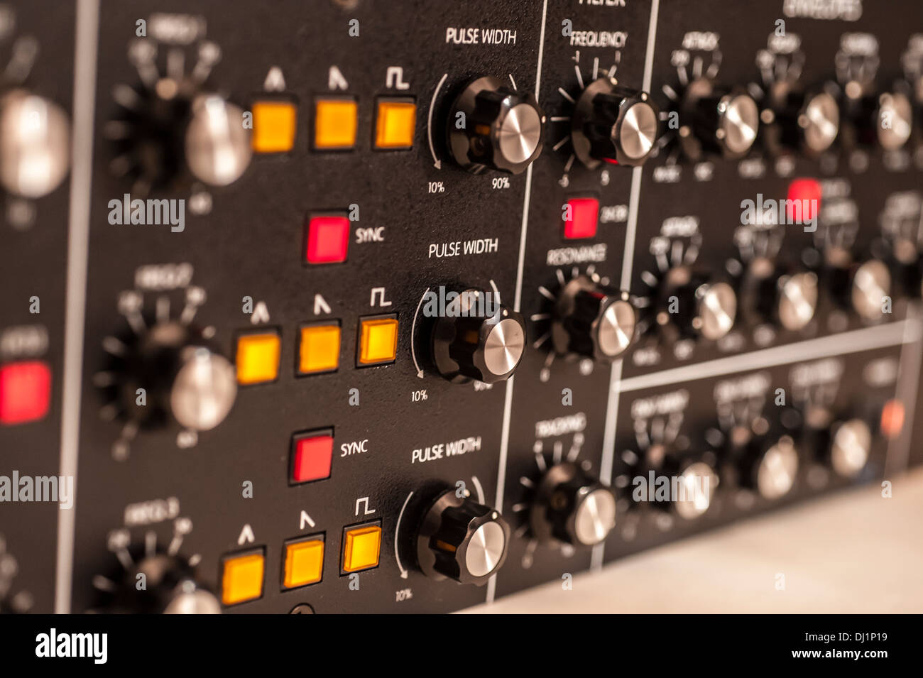 Analog synthesizer with knobs and buttons, partly blurred. Stock Photo
