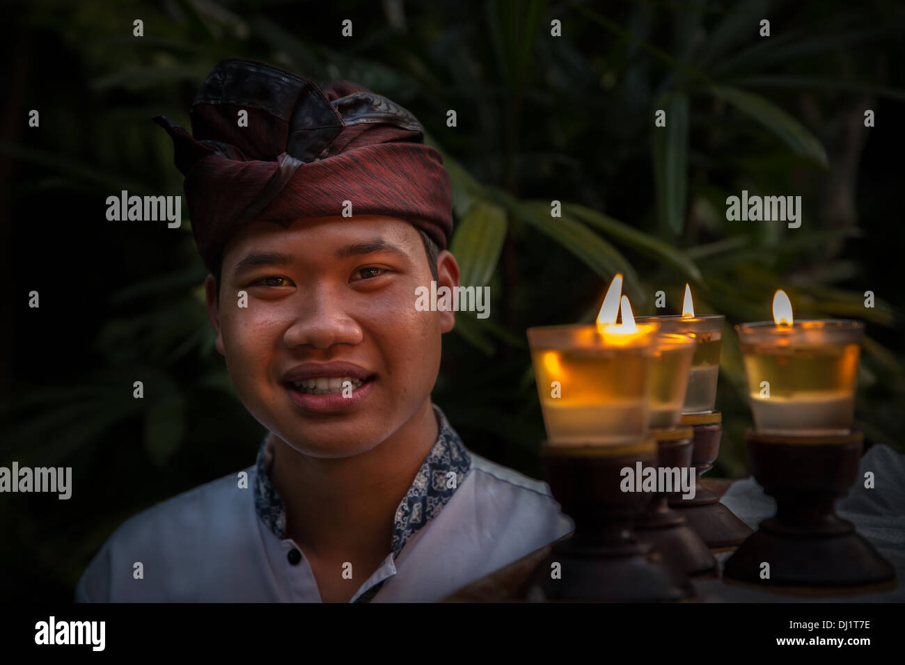 A Balinese man in traditional clothing carrying candles, Ubud, Bali, Indonesia, Asia - Stock Image