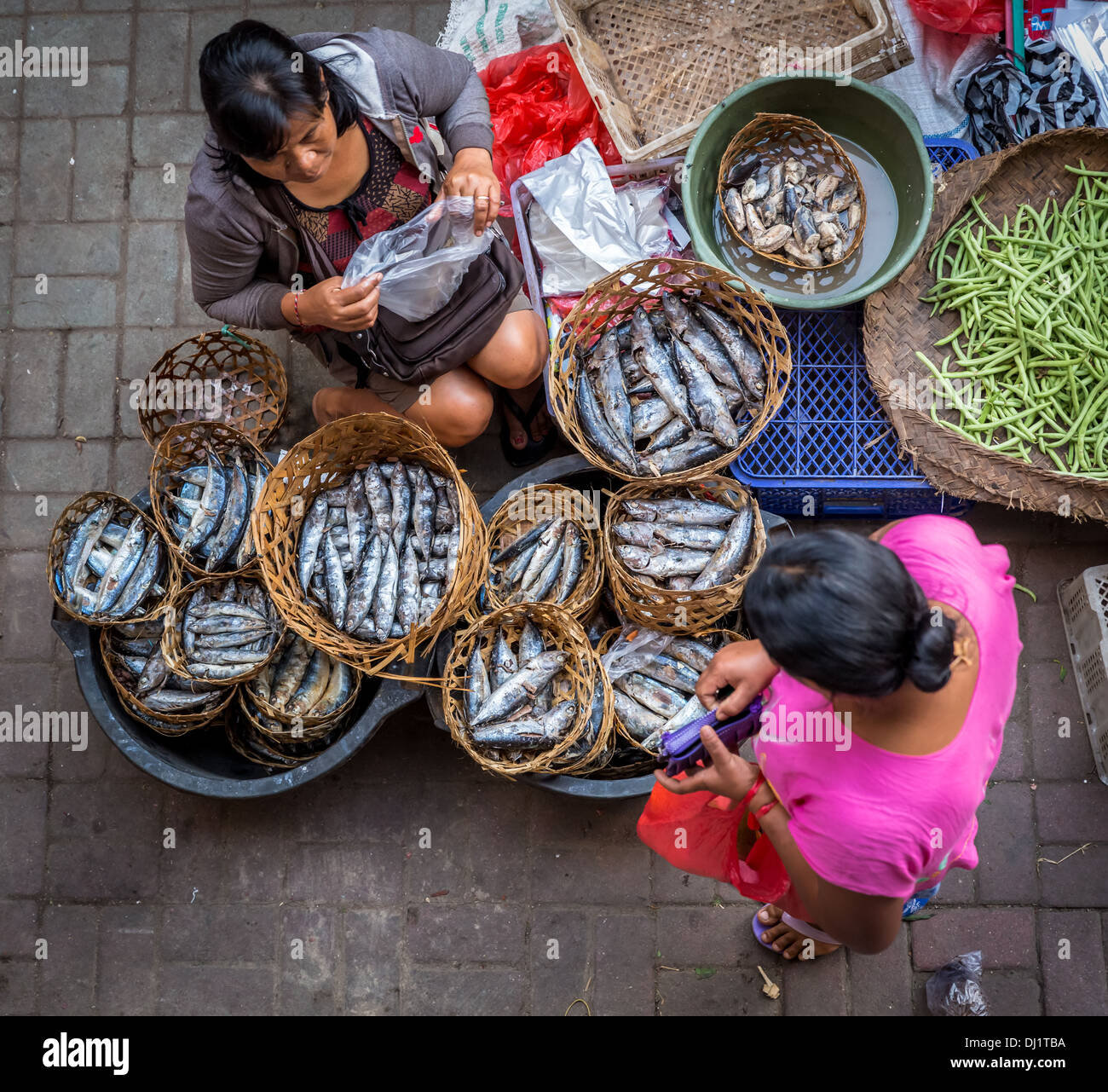 Woman selling fish at the local market in Ubud, Bali, Indonesia - Stock Image