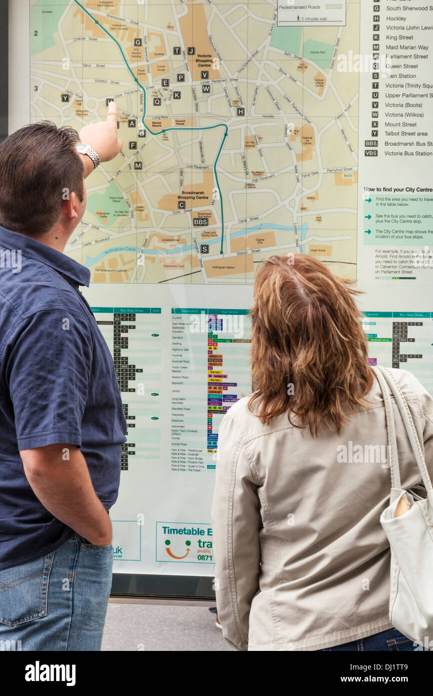 Two people looking at a city centre street map in Nottingham, England, UK - Stock Image