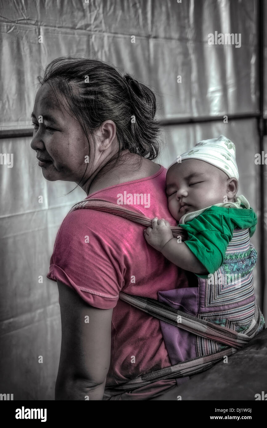 Thai mother carrying infant child in a back sling. Thailand S. E. Asia - Stock Image