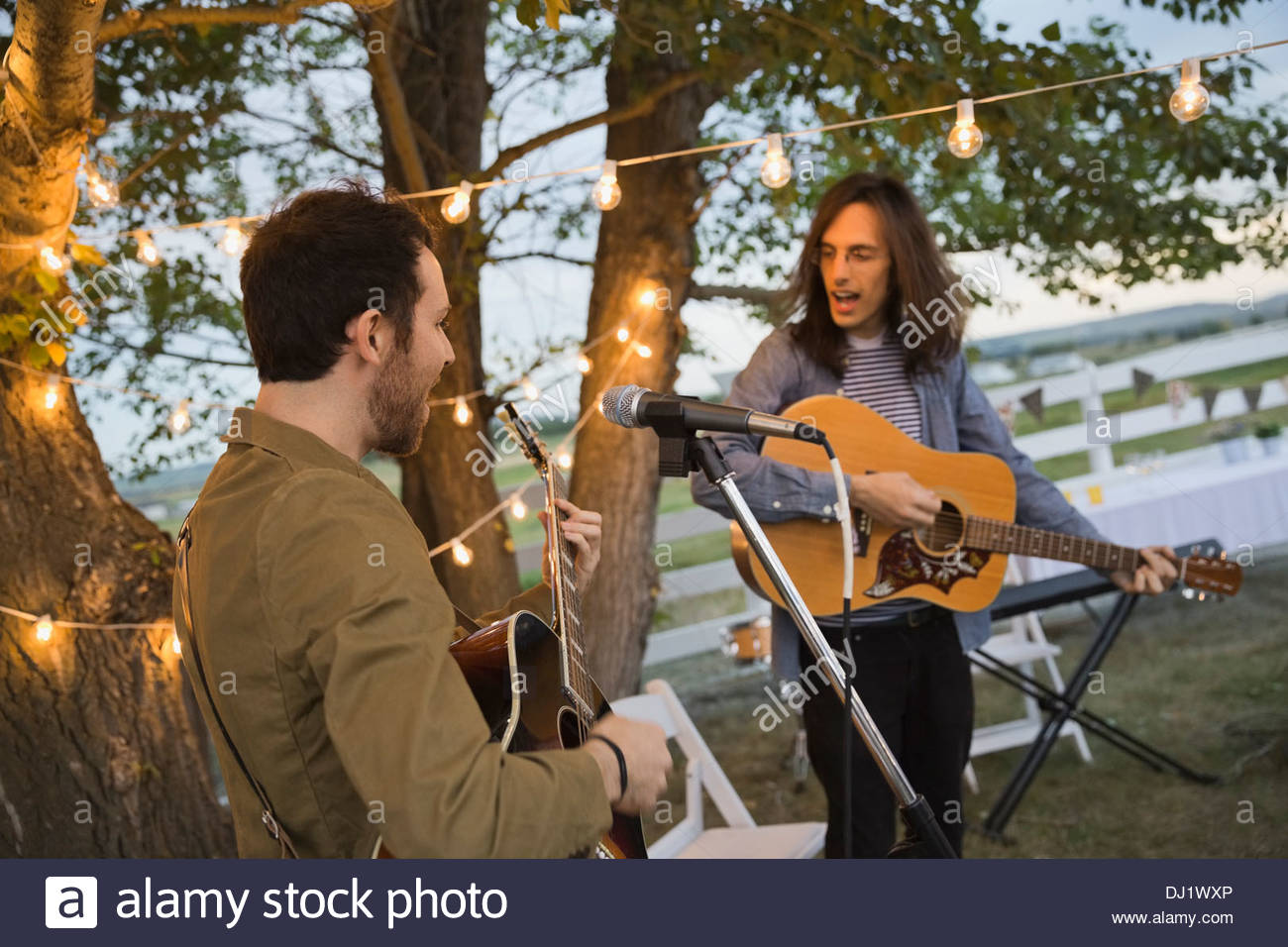 Men singing while playing guitars during outdoor party - Stock Image