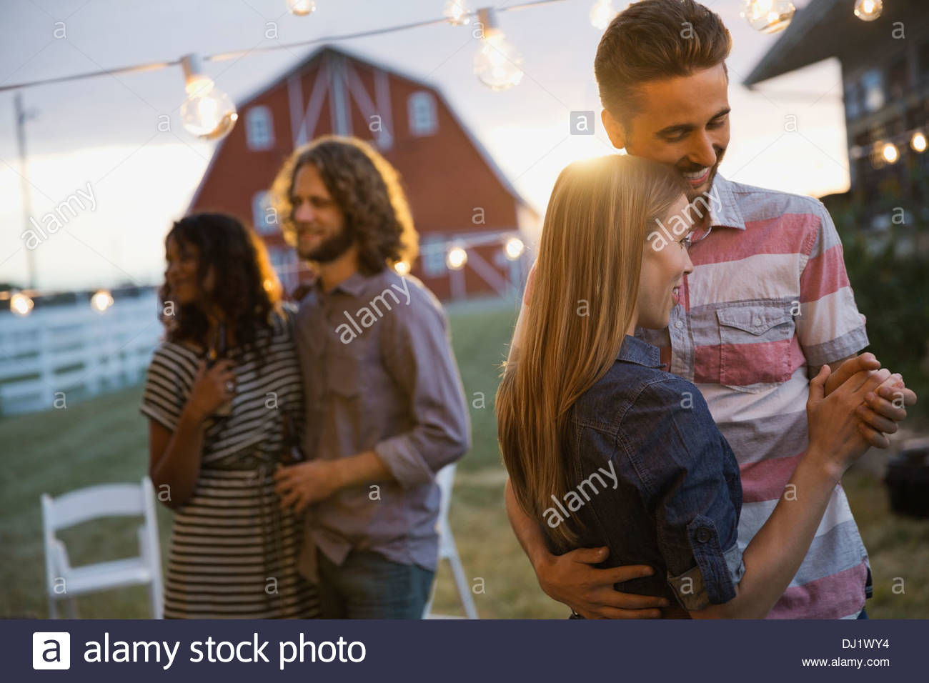 Young couples dancing on outdoor field at dusk - Stock Image