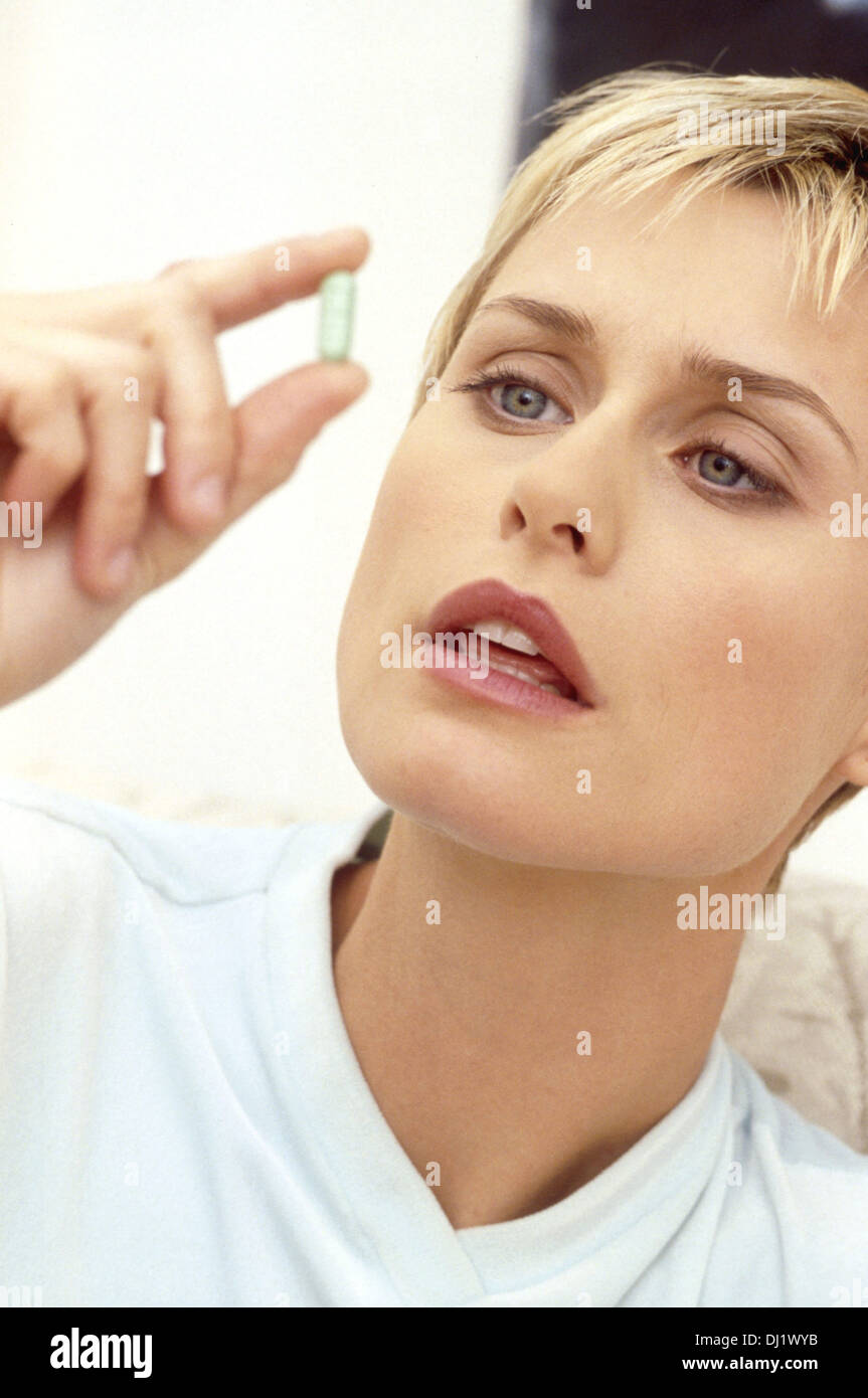 Blonde Woman examining pill looking closely - Stock Image