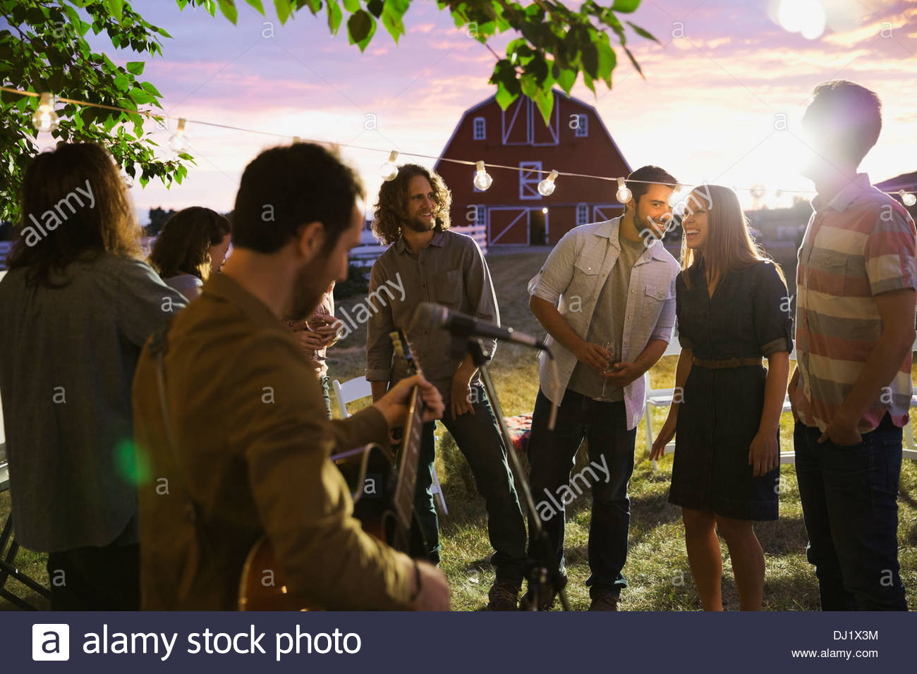Friends watching band play at outdoor farm party - Stock Image
