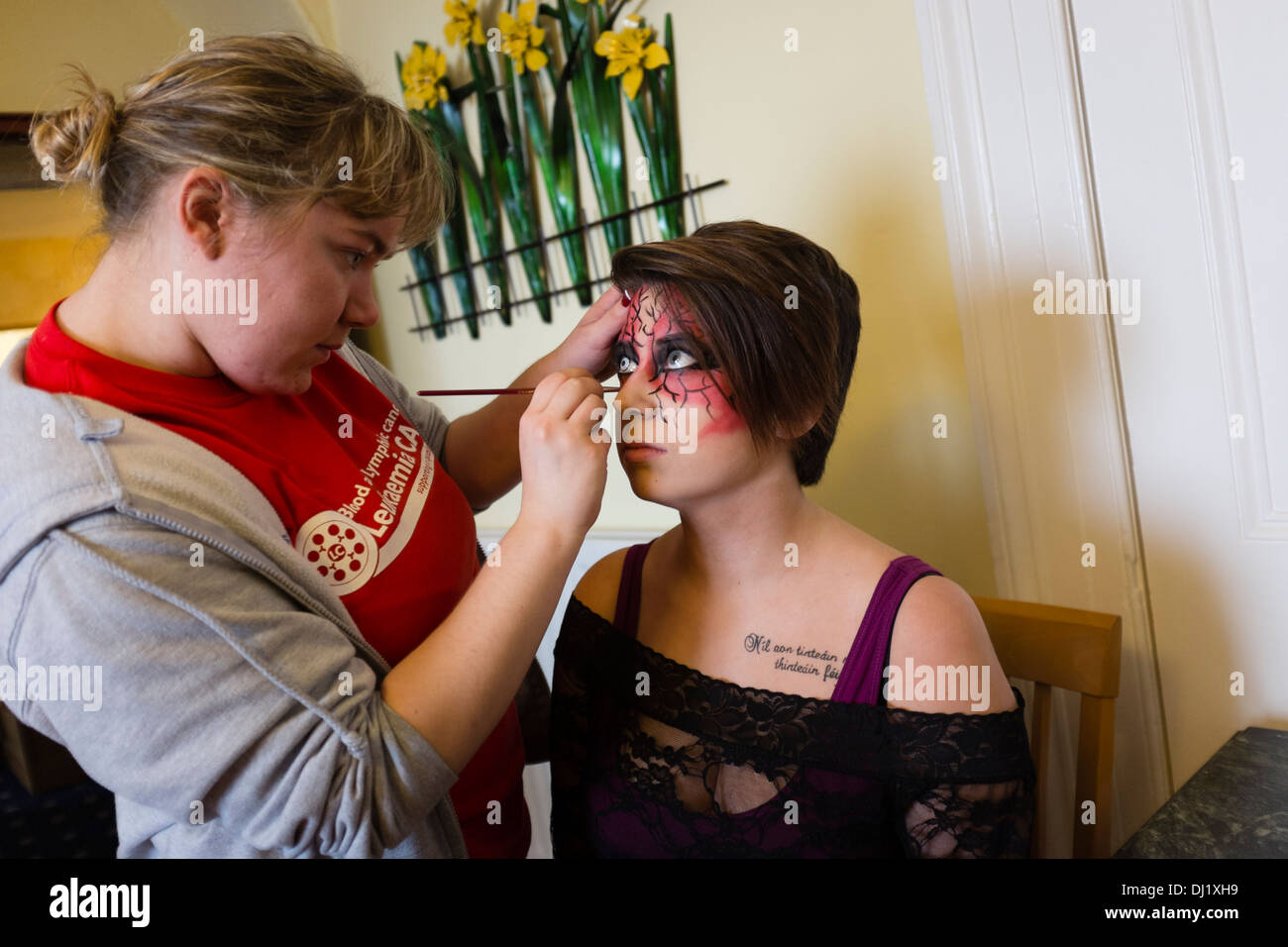 A woman applying makeup to a model's face backstage at a charity fashion show in aid of Leukaemia Care. UK - Stock Image