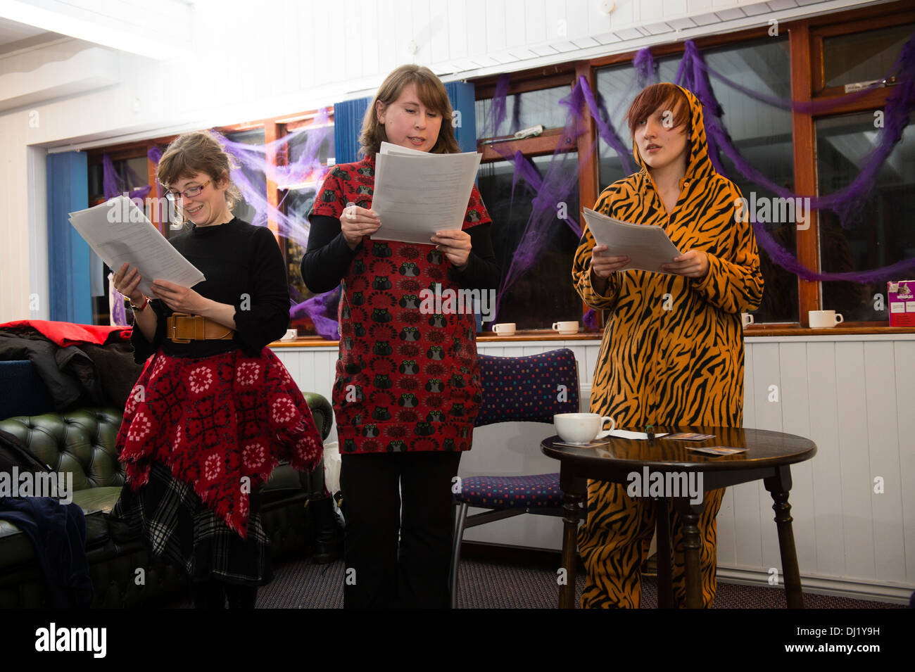 Three amateur women actors reading their scripts in a rehearsal for a theatre drama play UK - Stock Image