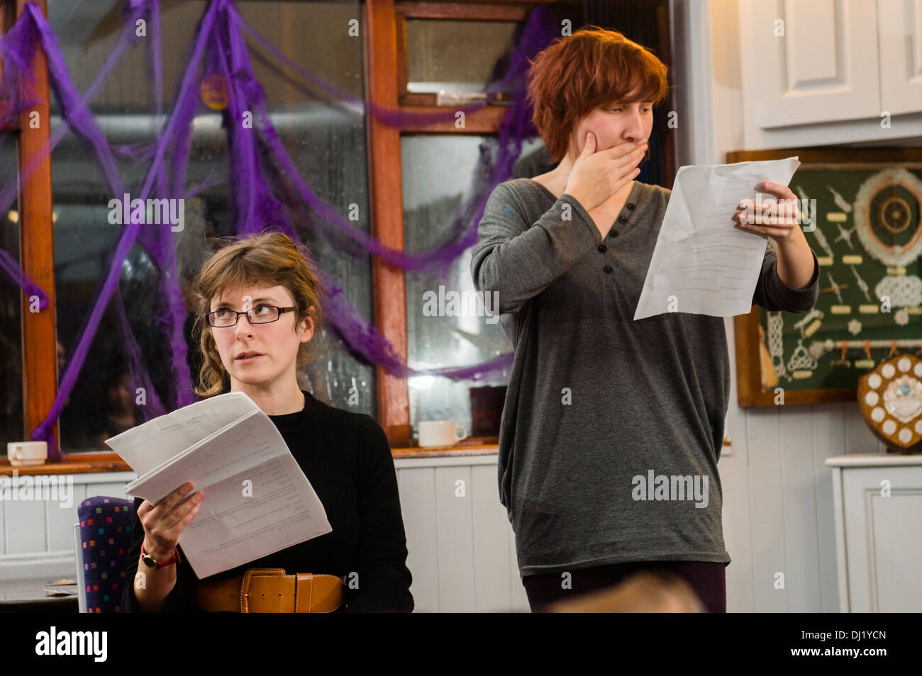 two amateur women actors reading their scripts in a rehearsal for a theatre drama play UK - Stock Image