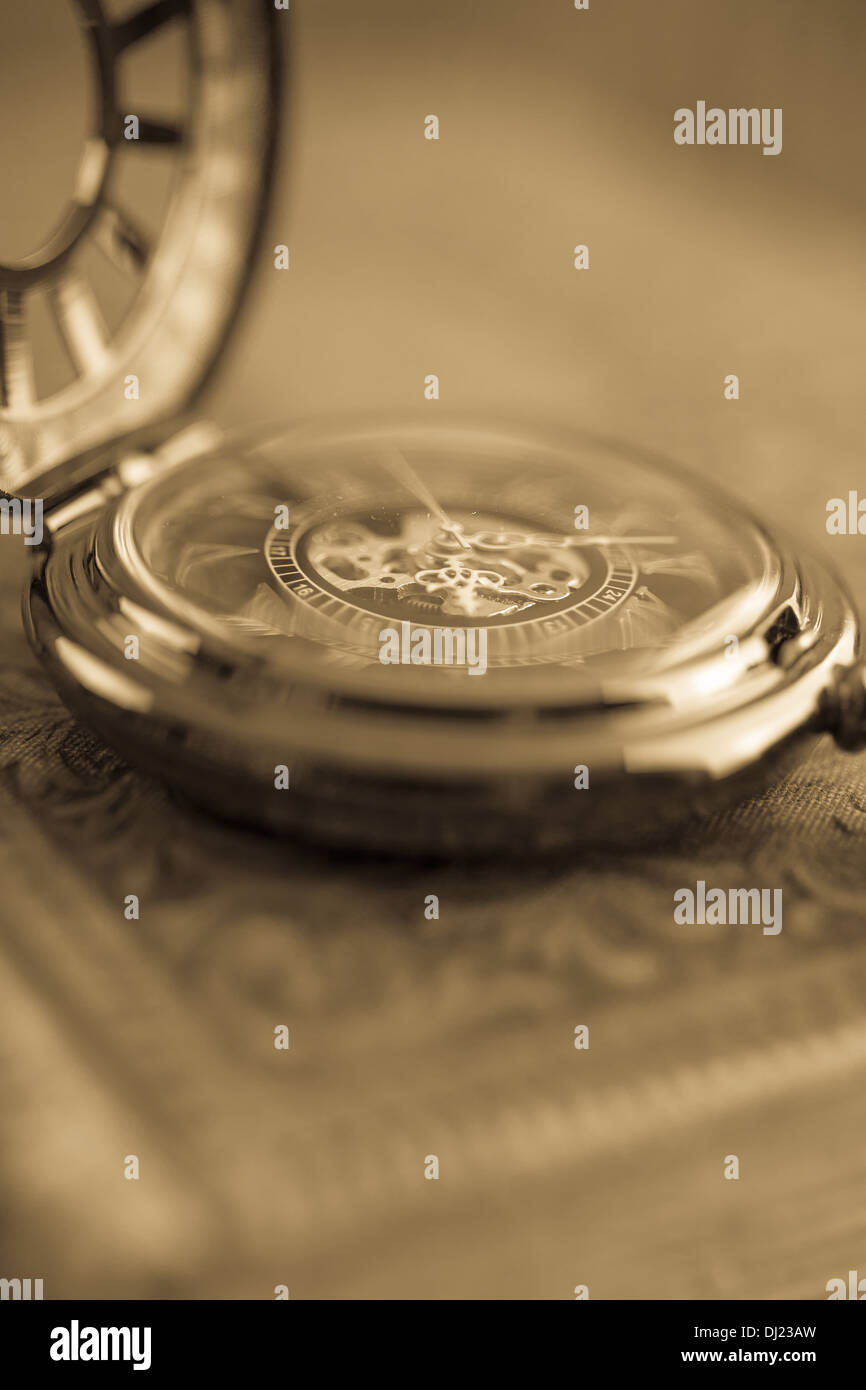 Blurry close up of a antique pocket watch with warm sepia tones. - Stock Image