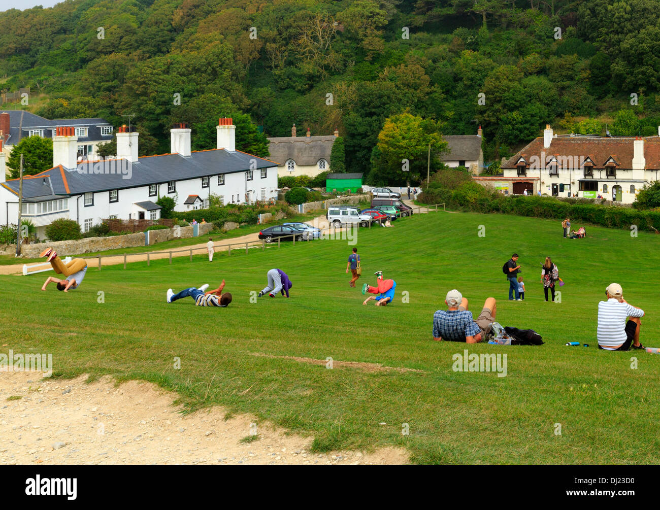 Teenagers on a school trip let off steam by somersaulting down a hill in Lulworth Cove, Dorset Stock Photo