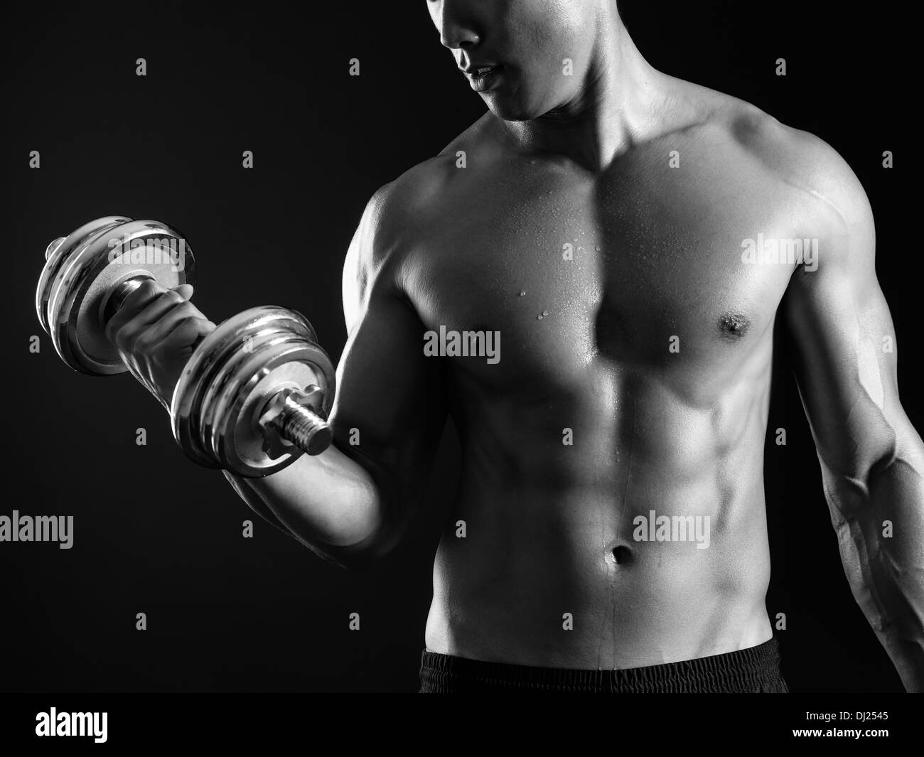 Photo of an Asian male exercising with a dumbbell and doing bicep curls over dark background. - Stock Image
