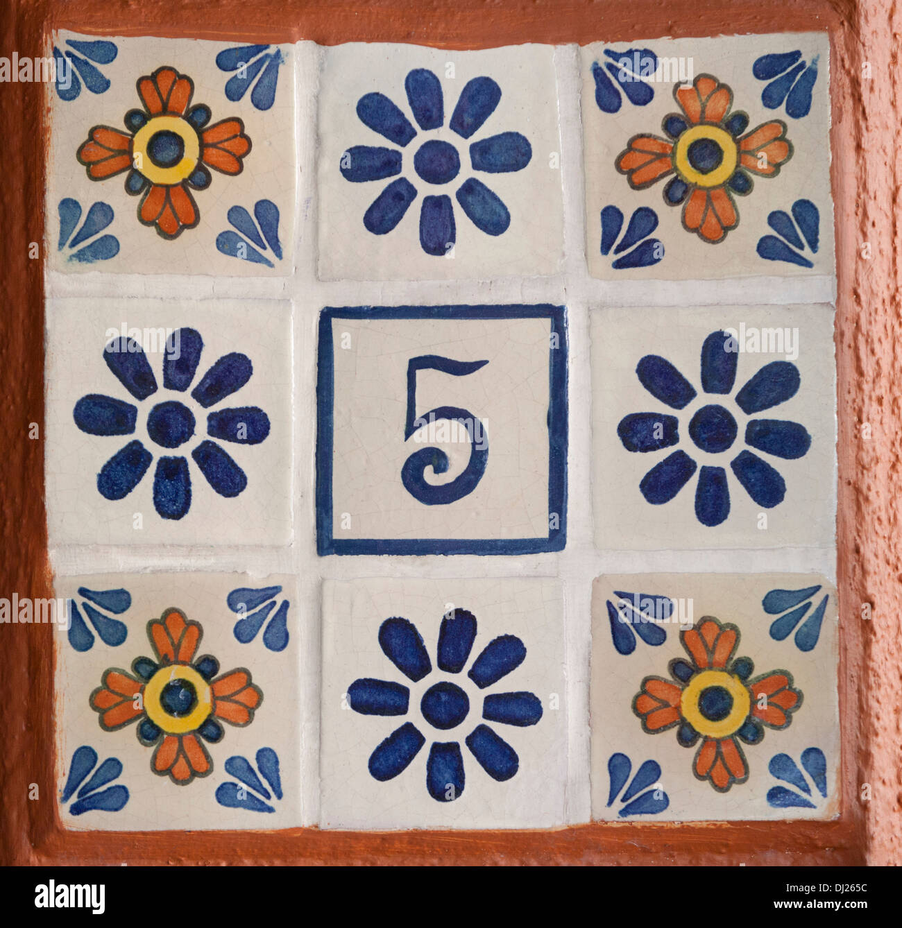 the number 5 set in hand painted tile amongst other floral tiles - Stock Image