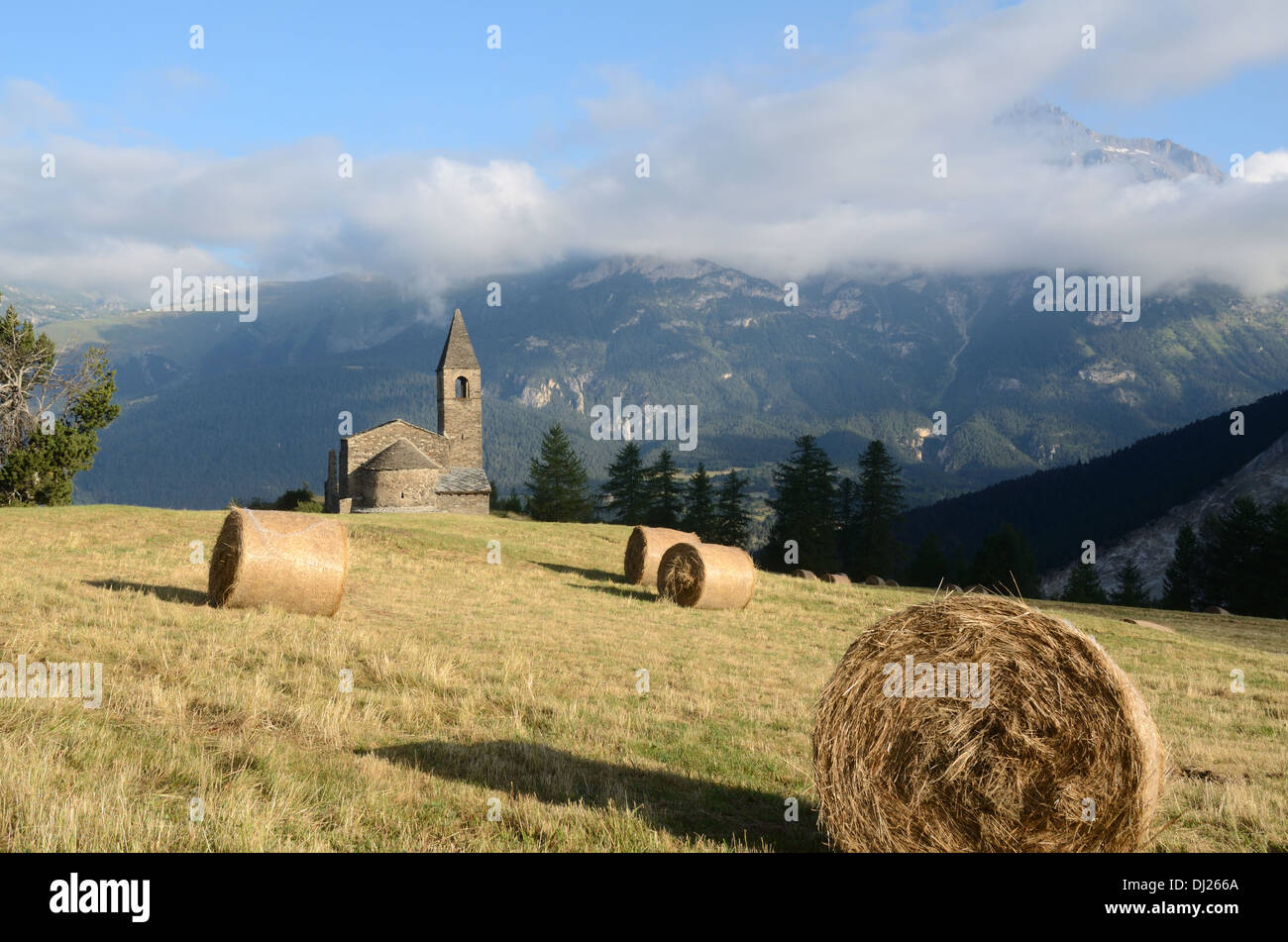 Church or Eglise St-Pierre Extravache and Hay Bales on Alpine Pasture Bramans Haute Maurienne Savoie France - Stock Image