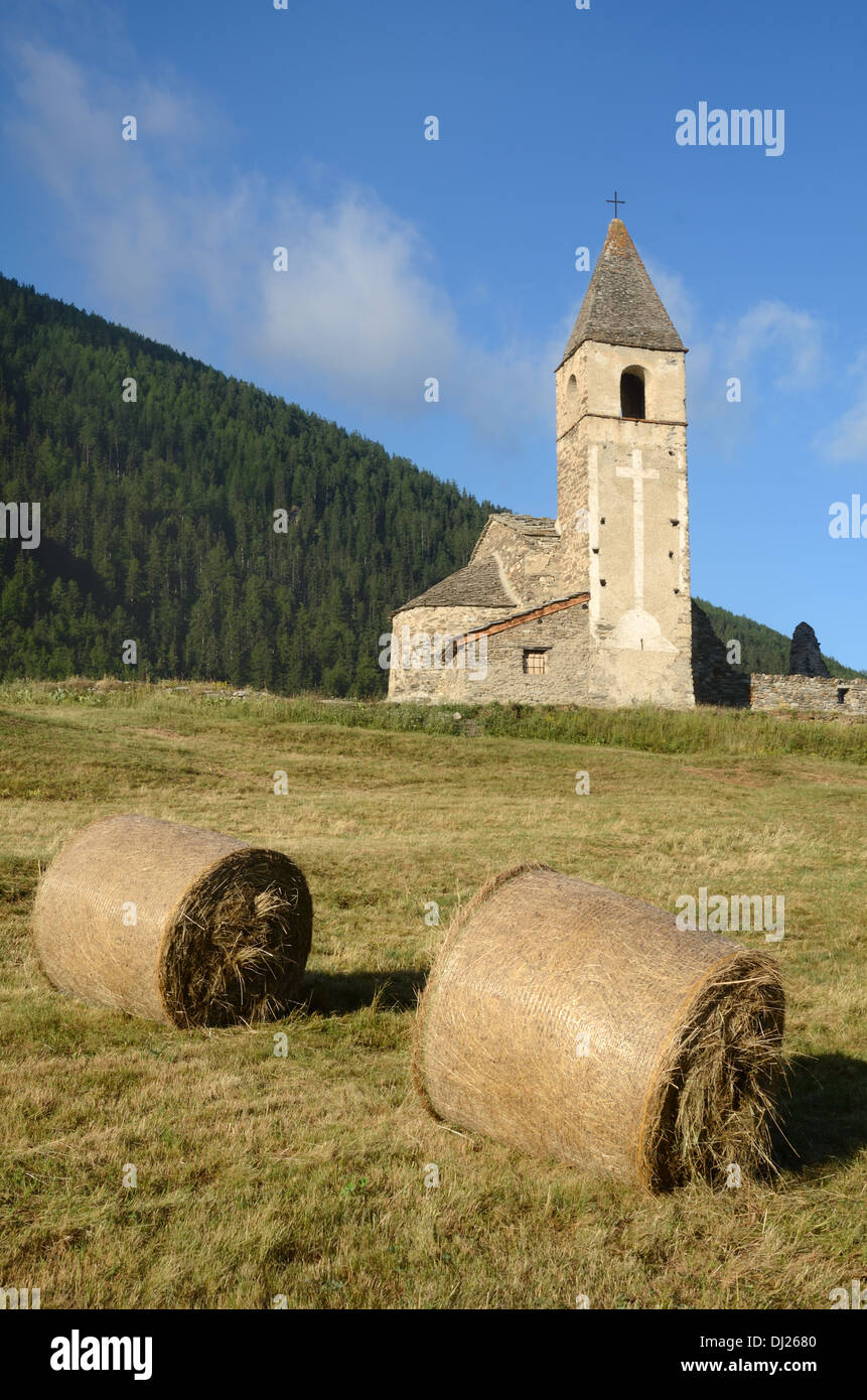 Hay Bales in front of Eglise St-Pierre d'Extravache Bramans Haute Maurienne Valley Savoie France - Stock Image