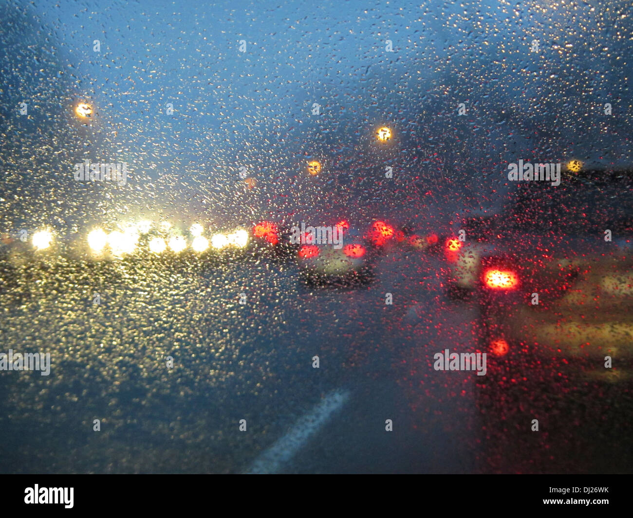 Driving on a highway at dusk in rush hour traffic with rain and mist gathering on the windshield. - Stock Image