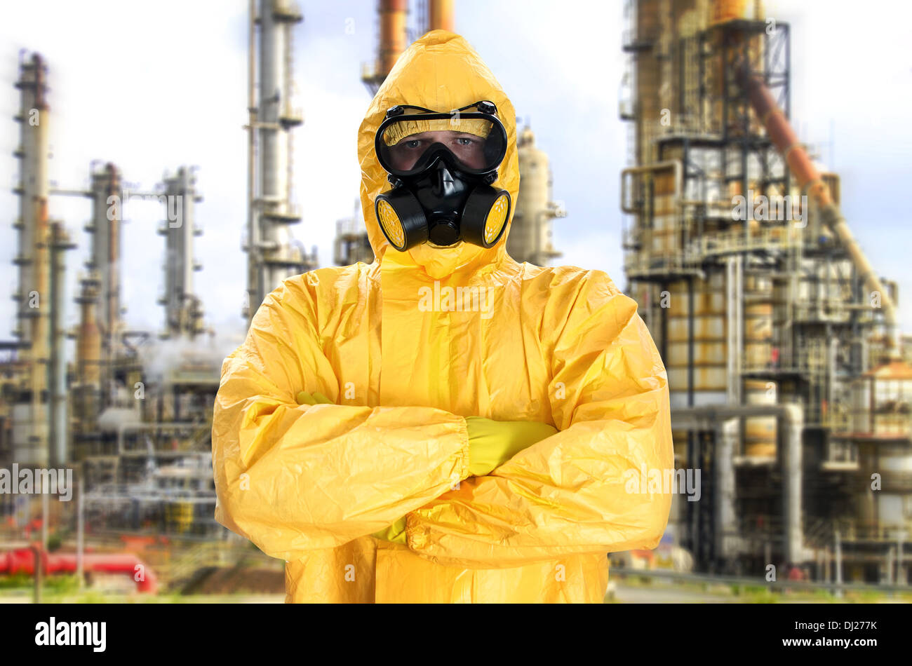 Man in chemical protective suit over factory - Stock Image