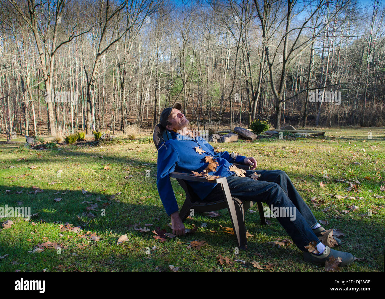 man smiling on lawn chair covered with leaves - Stock Image