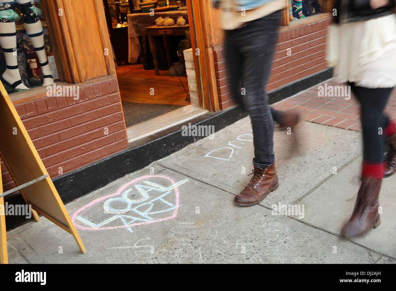 Pedestrians on Biltmore Avenue walk past a chalk drawing promoting local art, Asheville, North Carolina, USA - Stock Image