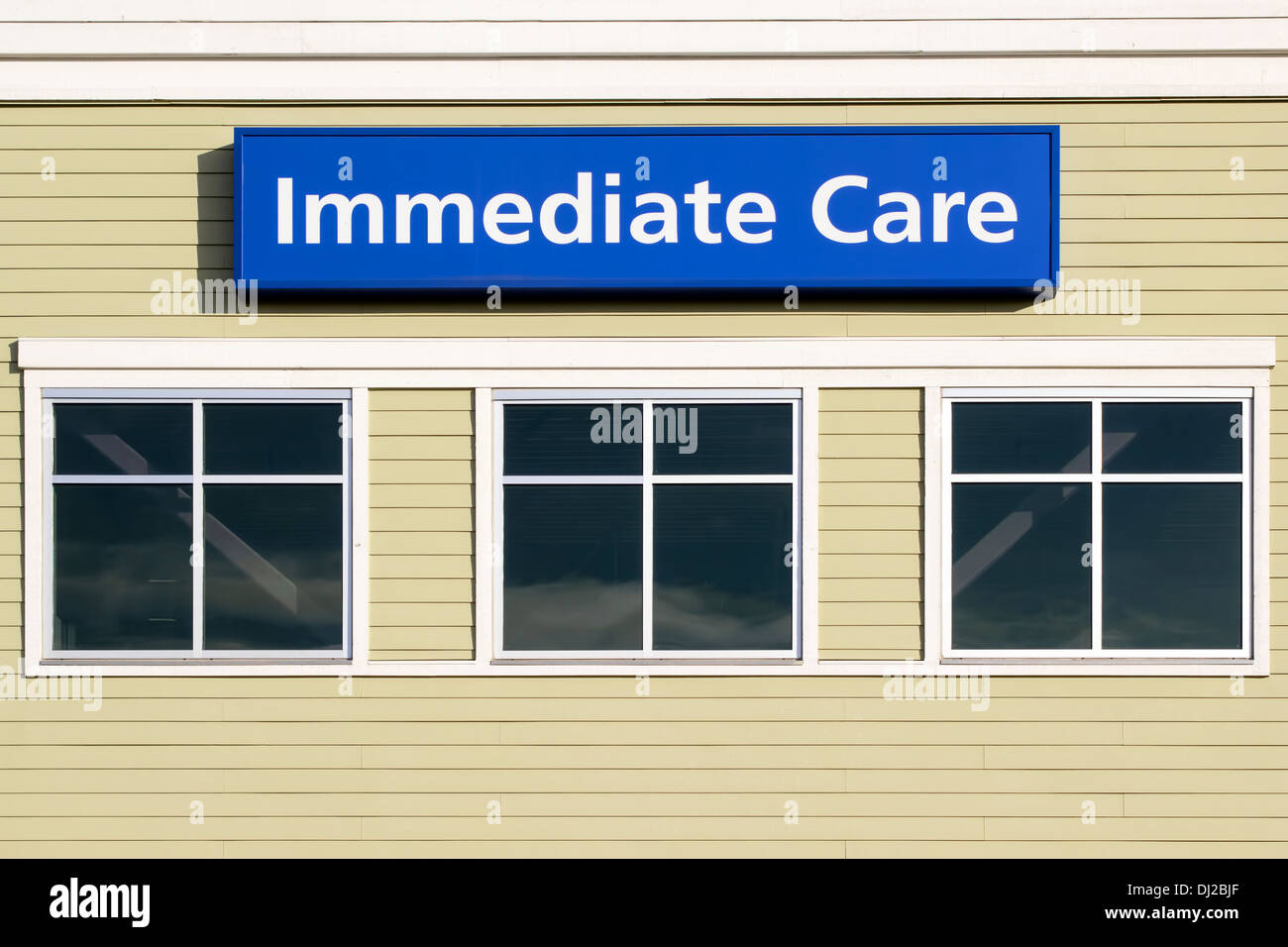 Immediate Care Sign Above Windows Outside Hospital or Emergency Clinic Building - Stock Image
