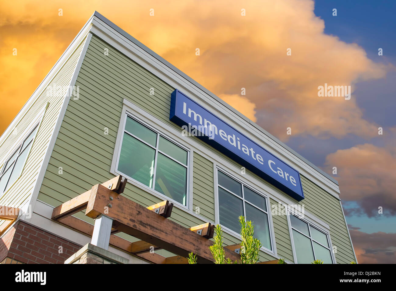 Immediate Care Sign Above Windows Outside Hospital or Emergency Clinic Building Against Sky with Clouds - Stock Image
